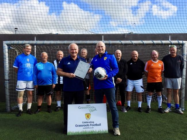 Gary is pictured with his honour as walking football participants look on.