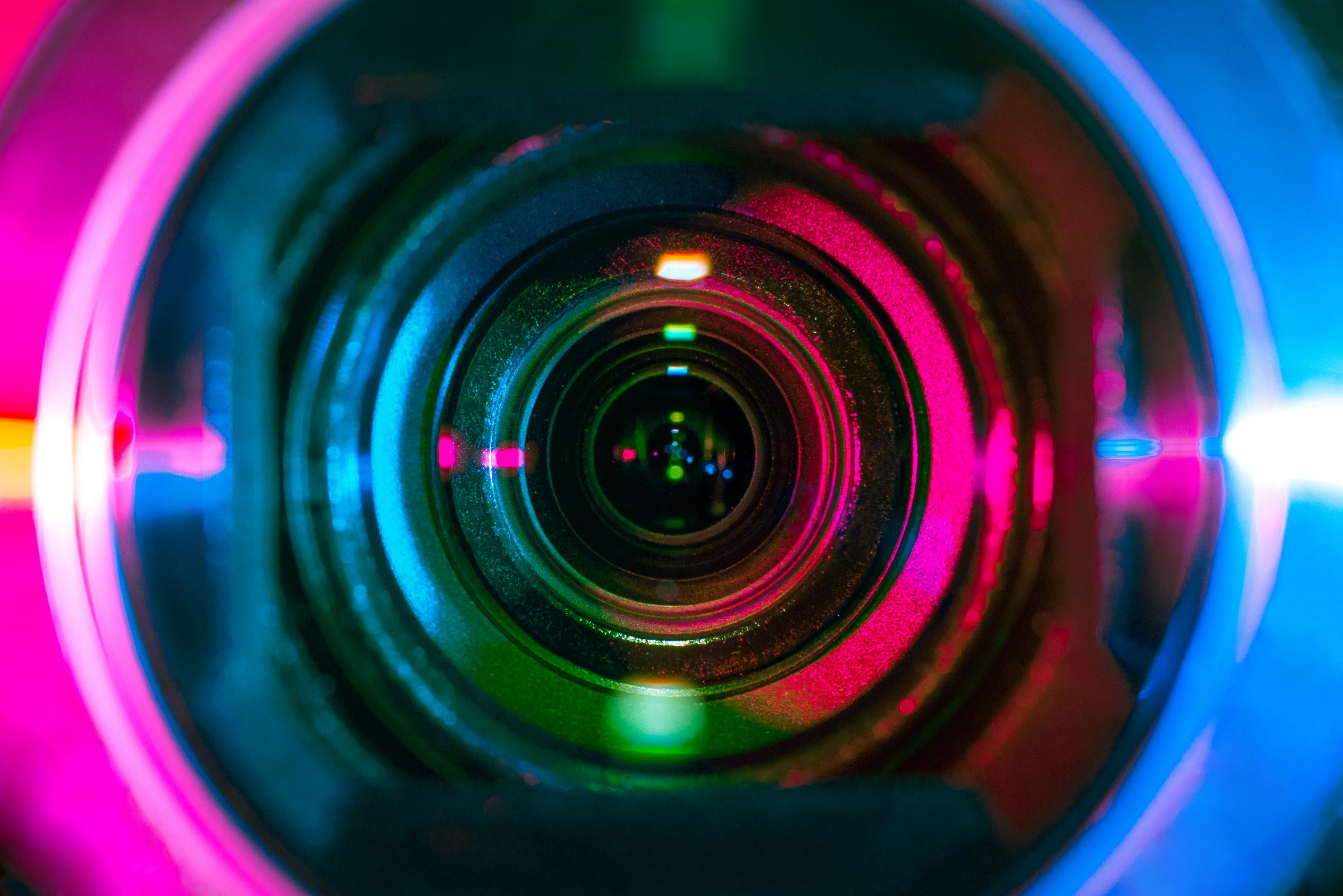 Video camera lens lit by different color light sources.